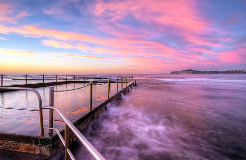The sky lights up pink and blue in a spectacular surmise at Mona Vale Tidal Pool, NSW, Australia