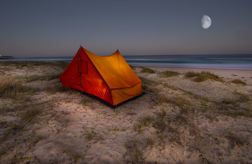 An Illuminated tent sits on sand dunes overlooking the ocean on the South Coast of NSW.