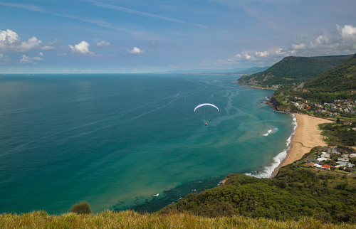 Parachuters jump from Bald Hill to land on the beach. Stanwell Gardens, Stanwell tops, Wollongong, NSW, Australia